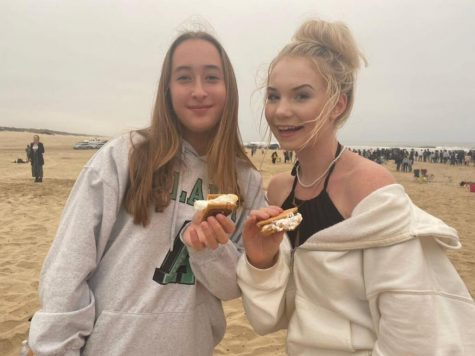 Paula, left, and Anne, right, enjoy a bonfire at the beach last weekend.  The two met at SMHS as new foreign exchange students. The two girls will be studying here until June.